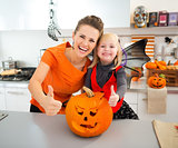 Halloween dressed girl with mother showing thumbs up in kitchen