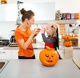 Halloween dressed girl with young mother scaring each other