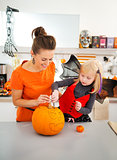 Happy mother with daughter creating Jack-O-Lantern on Halloween