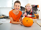 Mother with halloween dressed daughter creating Jack-O-Lantern