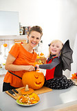 Mother with halloween dressed daughter carving Jack-O-Lantern