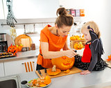 Mother with daughter carving Jack-O-Lantern for Halloween party
