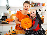 Mother with daughter holding big orange pumpkin Jack-O-Lantern