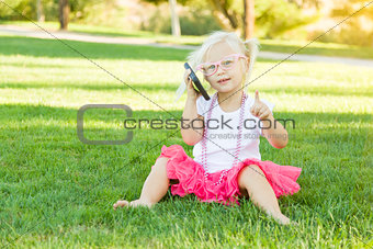 Little Girl In Grass Talking on Cell Phone