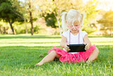 Little Girl In Grass Playing With Cell Phone