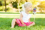 Little Girl In Grass Blowing On Pinwheel