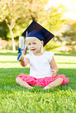 Little Girl In Grass Wearing Graduation Cap Holding Diploma With