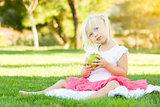Little Girl In Grass Eating Healthy Apple