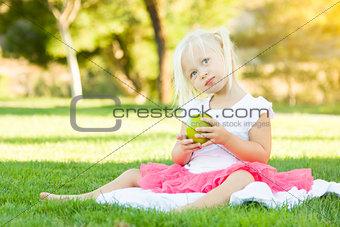 Little Girl In Grass Eating Healthy Apple