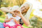 Little Girl With Mother Making Heart Shape with Hands