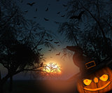 3DHalloween landscape of trees against a sunset sky