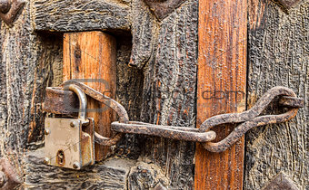Old styled rusty chain door lock on the wooden door