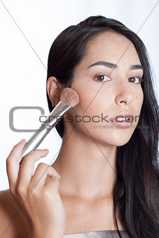 Beautiful girl with makeup brush on her face