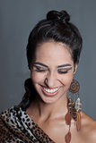 Smiling indian girl leopard spotted makeup and feathers earring