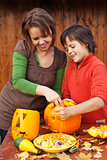 Young boy and woman carving a jack-o-lantern