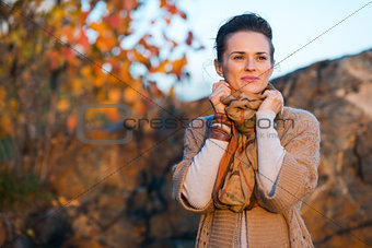 Smiling brown-haired woman relaxing in autumn park