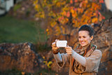 Woman taking photo with mobile while relaxing in autumn park