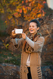 Woman taking photo with cell phone in autumn outdoors in evening