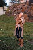 Laughing urban elegant woman walking in evening autumn park