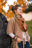 Portrait of relaxed woman near stone rock in evening autumn park