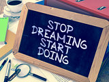 Stop Dreaming Start Doing. Motivational Quote on Chalkboard.
