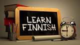 Hand Drawn Learn Finnish Concept on Chalkboard.