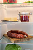 Open fridge stuffed with salami and foodstuffs