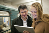 Happy young people with touch pad in subway