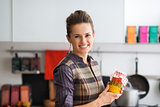 Smiling woman holding jar of vegetables in kitchen