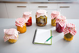Jars of preserved vegetables on kitchen counter with notepad