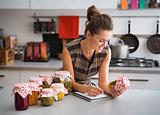 Woman in kitchen listing ingredients in vegetable preserves