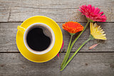 Cup of coffee and gerbera flowers