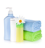 Shampoo and gel bottles with towels and flower