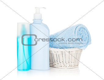 Cosmetics bottles and blue towel
