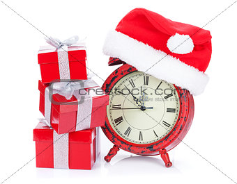 Christmas clock, gift boxes and santa hat