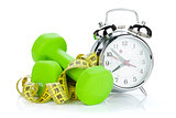 Two green dumbells, tape measure and alarm clock