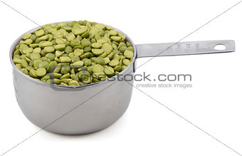 Green split peas in a measuring cup