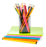 Pencil cup with crayons on copybooks