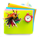 Crayons and alarm clock on copybooks