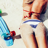 sexy suntanned lady with the blue penny board lying on the beach