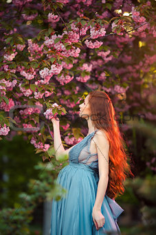 Beautiful pregnant woman in blooming garden