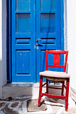 Detail of colorful blue door and red wooden chair