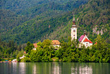 Island with Catholic Church on Bled Lake in Slovenia. Hill with Forest in Background.