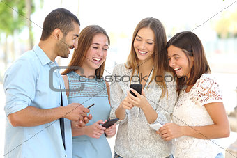 Four friends watching social media in a smart phone