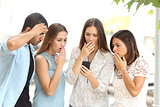 Four worried friends watching smart phone