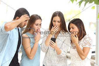 Four worried friends watching smart phone