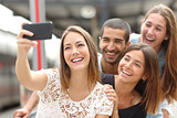 Group of four friends taking selfie with a smart phone