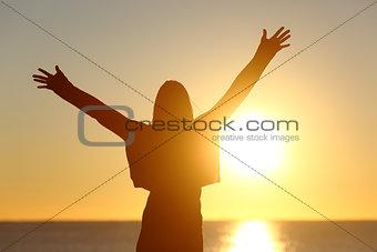 Free woman raising arms watching sun at sunrise