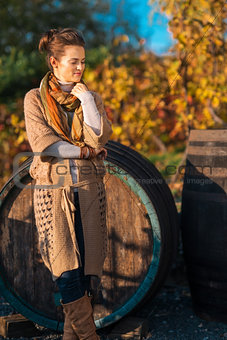 Portrait of relaxed woman winemaker standing in autumn vineyard