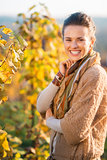 Smiling woman winegrower standing in vineyard outdoors in autumn